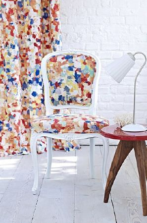Prestigious Textiles -  Printworks Fabric Collection - Painted effect blue, red, orange and white curtains with a matching chair with a white wood frame, with a table and a lamp