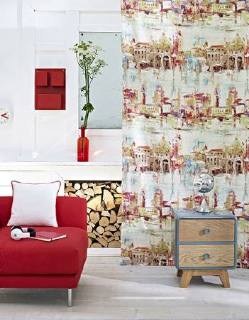 Prestigious Textiles -  Printworks Fabric Collection - Red chair with a white cushion, multicoloured buildings printed on a long curtain, a set of drawers in wood and light blue