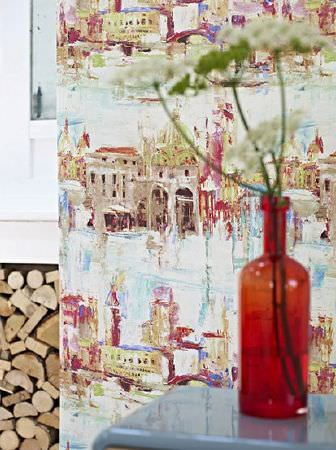 Prestigious Textiles -  Printworks Fabric Collection - A red glass bottle vase with flowers on a light blue surface in front of a backdrop with paintings of buildings and rivers
