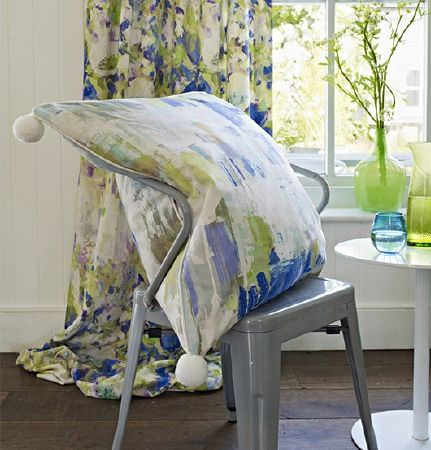 Prestigious Textiles -  Printworks Fabric Collection - White pompoms on a blue, green and white streaked cushion, on a grey chair with a white table andbright floral curtains
