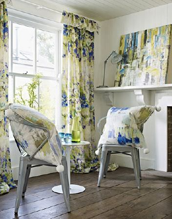 Prestigious Textiles -  Printworks Fabric Collection - Blue, green and white streaks covering curtains, large cushions with pompoms, artwork, with grey chairs, a table and a lamp