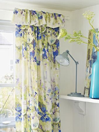 Prestigious Textiles -  Printworks Fabric Collection - Curtains made with abstract cream, blue and green florals, with a grey anglepoise lamp and an aqua blue bottle vase