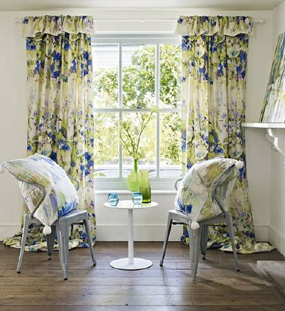 Prestigious Textiles -  Printworks Fabric Collection - Grey chairs and a white table, with large cushions and curtains with white, blue and greenstreaks and abstract florals