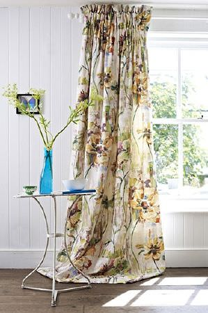 Prestigious Textiles -  Printworks Fabric Collection - Large gold, dusky pink and light green floral patterned floor-length curtainswith a round white metal table and a blue vase