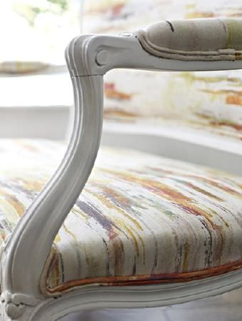 Prestigious Textiles -  Printworks Fabric Collection - Grey, orange, cream and gold streaks patterning the back, seat and armrest of a white sofa with a white wood frame