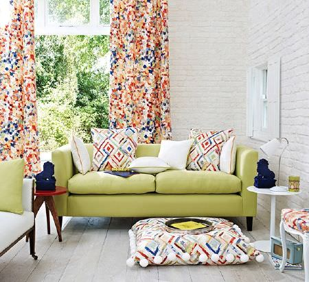 Prestigious Textiles -  Printworks Fabric Collection - Light green and white sofas with white, orange, blue and gold patterned curtains and cushions, two round tables and a lamp