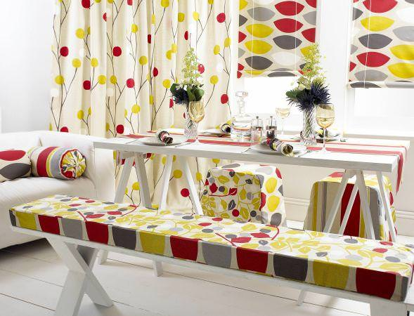 Prestigious Textiles -  Richmond Park Fabric Collection - Bench seating pads with a modern green and red leaf pattern, stool covers, a red striped tablecloth, and modern curtains and roman blinds