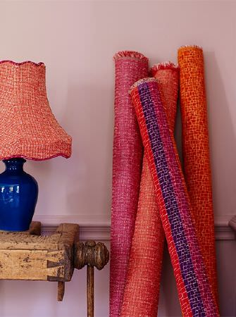 Prestigious Textiles -  Rocco Fabric Collection - A wooden table, blue lamp with a bright coral shade, and four rolls of bright pink, coral, orange and bold striped fabrics