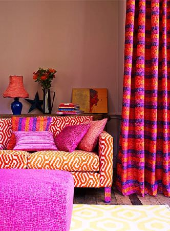 Prestigious Textiles -  Rocco Fabric Collection - Patterned and striped fabrics making bold cushions, curtains, a sofa and a footstool in vivid pink, purple, coral and orange