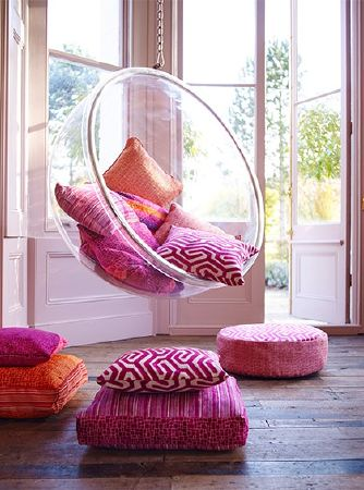 Prestigious Textiles -  Rocco Fabric Collection - A clear suspended bubble chair with patterned scatter and floor cushions in vivid pink, purple, coral and orange colours