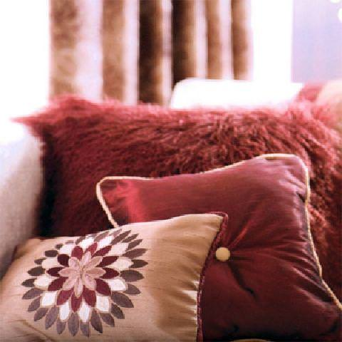 Prestigious Textiles -  Rodeo Fabric Collection - A pink cushion with a red central flower and red edges, a red cushion woth a pink button and pink edges, and a big furry cushion