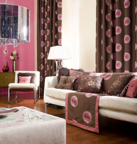 Prestigious Textiles -  Rodeo Fabric Collection - Dark brown curtains with a pink flower pattern, a white upholstered couch with brown cushions with modern flower designs for a modern home