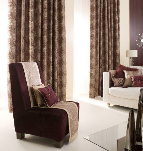 Prestigious Textiles -  Rodeo Fabric Collection - Curtains made from slightly reflective brown fabric with a modern pink and dark brown floral design, dark red upholstered chair with cushion