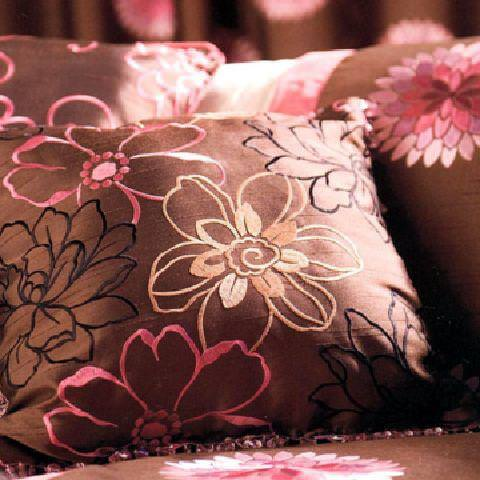 Prestigious Textiles -  Rodeo Fabric Collection - A close-up picture of a brown cushion with a modern white, pink and black floral pattern