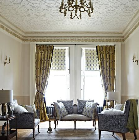 Prestigious Textiles -  Safari Fabric Collection - Elegant blue 7 white patterned armchairs, a white sofa with a wood frame, cushions, diamond print blinds and gold curtains