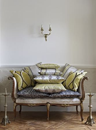 Prestigious Textiles -  Safari Fabric Collection - A silver sofa with an ornate bronze frame, with 10 scatter cushions with dark grey, champagne, green and silver patterns