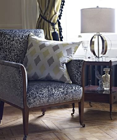 Prestigious Textiles -  Safari Fabric Collection - A wood frame on a charcoal and silver patterned padded armchair with a diamond print cushion, by a wooden table and a lamp