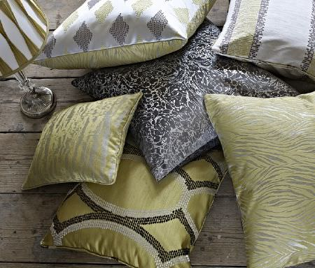 Prestigious Textiles -  Safari Fabric Collection - A silver lampstand with a shade and six scatter cushions, all covered with various light gold, charcoal and silver patterns