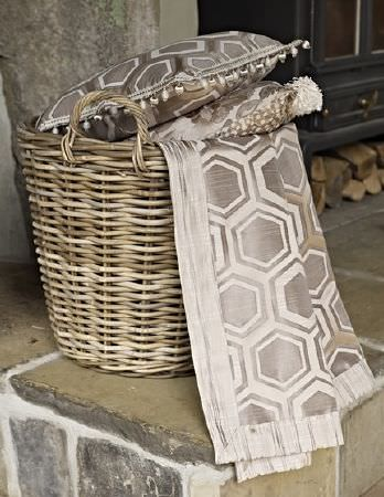Prestigious Textiles -  Samarkand Fabric Collection - A wicker basket holding a throw and two cushions, all featuring florals, hexagons and geometric prints in cream and silver