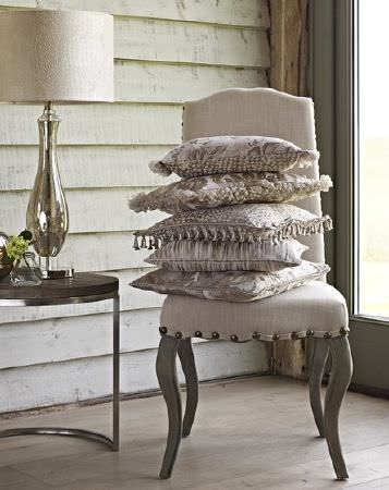 Prestigious Textiles -  Samarkand Fabric Collection - A table with a curved metal base, a white and silver lamp, a white chair with grey legs, and 5 cream patterned cushions