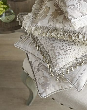 Prestigious Textiles -  Samarkand Fabric Collection - 5 cushions with subtle silver and white florals, patterns and stripes, with some fringing, on a white chair with grey legs