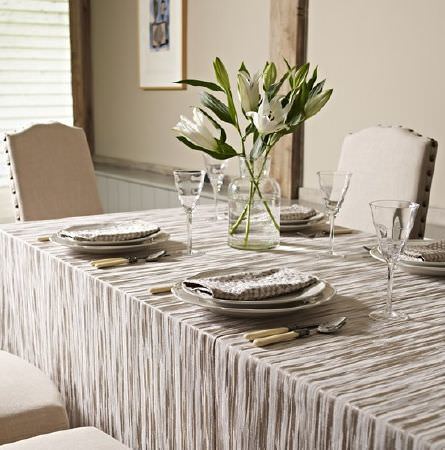 Prestigious Textiles -  Samarkand Fabric Collection - A grey and white streaked tablecloth on a large table with plain ivory coloured padded chairs, crockery, glasses and a vase