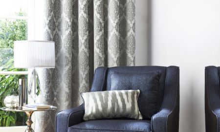 Prestigious Textiles -  San Marco Fabric Collection - Navy blue corner chair with matching silver cushion and curtain, shiny fabric with diamond and animal print pattern