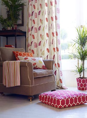 Prestigious Textiles -  Secret Garden Fabric Collection - A brown-grey armchair with multicoloured fern print curtains, patterned cushions and fabric, and a red and white floor cushion