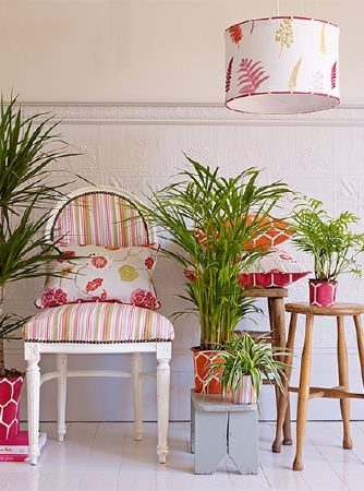 Prestigious Textiles -  Secret Garden Fabric Collection - Patterned flowerpots with a ceiling lightshade, cushion and padded armchair in white, pink, orange, red and green