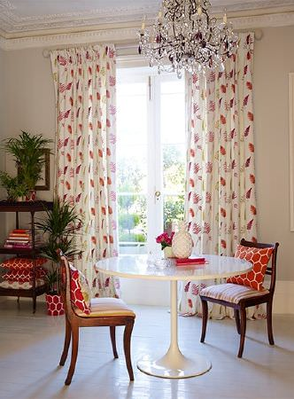 Prestigious Textiles -  Secret Garden Fabric Collection - Orange and white geometric print cushions, white, pink and orange fern print curtains, a round white table and wooden chairs