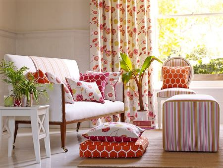 Prestigious Textiles -  Secret Garden Fabric Collection - Striped, geometric print, floral and plain fabrics in white, orange, pink and green on a sofa, cushions and curtains