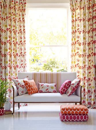 Prestigious Textiles -  Secret Garden Fabric Collection - Floor-length floral curtains with a simple white sofa and pink, orange, white and green geometric print and floral cushions
