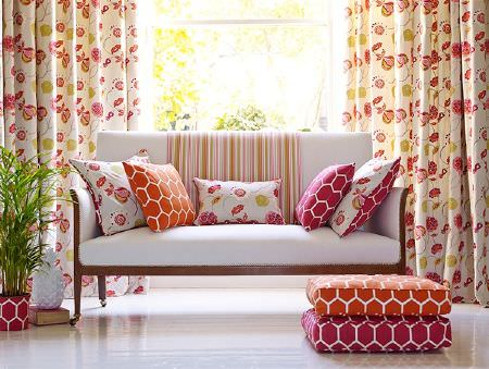 Prestigious Textiles -  Secret Garden Fabric Collection - Geometric print and floral cushions in bright pink and orange, with striped fabric, on a white sofa with floral curtains