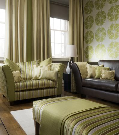 Prestigious Textiles -  Sierra Fabric Collection - Plain lime green curtains behind a green and white striped upholstered armchair with green cushions, and a striped upholstered footstool