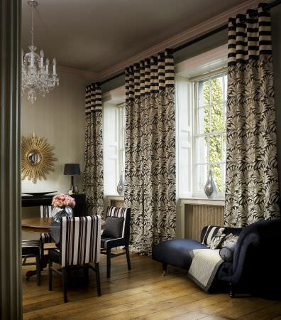 Prestigious Textiles -  Sierra Fabric Collection - Black curtains with white striped tops and leaf patterned bottom, upholstered striped dining chairs, and a black lounger with a white quilt