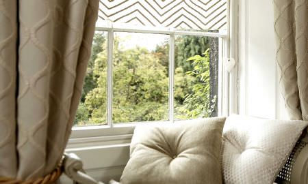 Prestigious Textiles -  Skandic Fabric Collection - Muted tones of cream and oatmeal with textured patterns in cushions and curtains, zigzag pattern cream and tan Roman blind to match