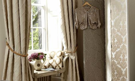 Prestigious Textiles -  Skandic Fabric Collection - Stylish window seat with cream and brown patterned cushion, floor lenght tan curtains