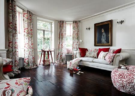 Prestigious Textiles -  Soleil Fabric Collection - White sofa, red and white patterned cushions, footstool, and curtains, a red wood trestle table, white side table and white anglepoise lamp