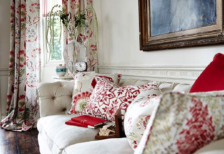 Prestigious Textiles -  Soleil Fabric Collection - Green, red and white patterned and floral cushions on an off-white sofa, with matching curtains, a large white vase and a clock