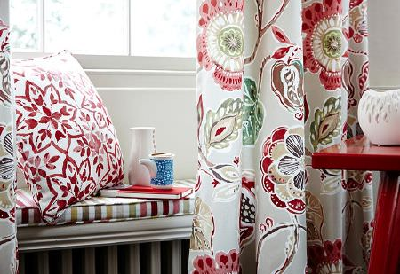Prestigious Textiles -  Soleil Fabric Collection - Bench seat cushion in coloured stripes, white curtains with large multicoloured florals, red and white cushion, red table and white bowl