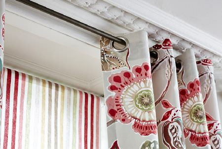 Prestigious Textiles -  Soleil Fabric Collection - Eyelet curtains in cream with red, pink, beige and green flowers, with blinds with red, pink, green, blue, gold and grey vertical stripes