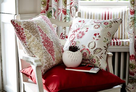 Prestigious Textiles -  Soleil Fabric Collection - White wood chair with three cushions in plain red, and red, green, gold and white patterns, with matching curtains and striped seat cushion