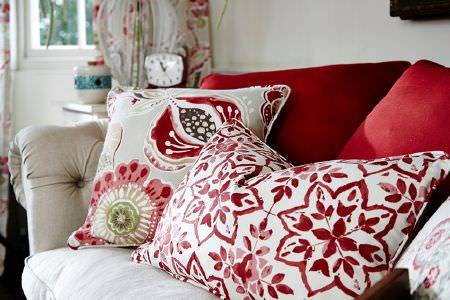 Prestigious Textiles -  Soleil Fabric Collection - Plain red cushions, red and white patterned cushion, floral cushion, on an off-white sofa, with floral curtains, white vase, and a clock