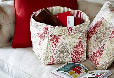 Prestigious Textiles -  Soleil Fabric Collection - Storage bag with green, red and white patterned fabric outer and striped inner, matching cushion, and a red cushion, all on a beige sofa