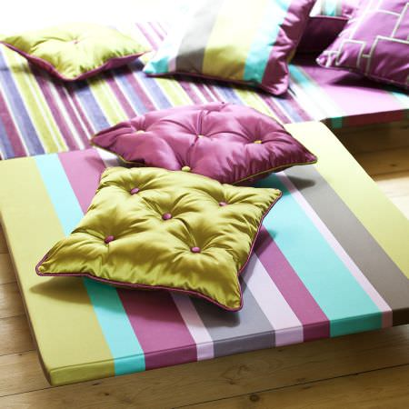 Prestigious Textiles -  Sophistication Fabric Collection - Vivid green and pink cushions made of reflective fabric and with buttons, and green, pink and teal striped seating pads