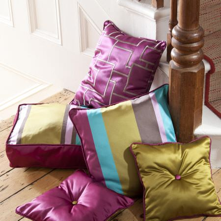 Prestigious Textiles -  Sophistication Fabric Collection - A plain pink and green cushion, green, pink and teal striped square cushions and a cushions with a geometric design