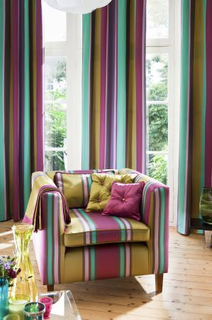 Prestigious Textiles -  Sophistication Fabric Collection - Modern curtains with teal, green, and pink curtains, a green, purple and teal stripe upholstery on an armchair, and cushions