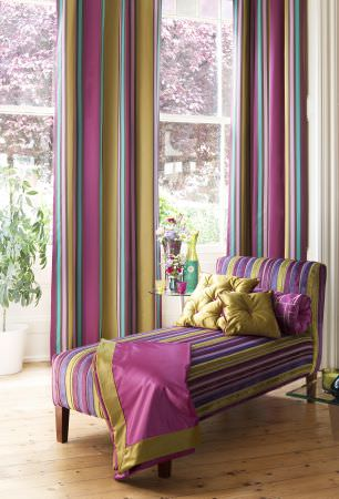 Prestigious Textiles -  Sophistication Fabric Collection - Green, pink, and teal striped curtains, and a green and pink striped upholstered lounger with green cushions for a modern house