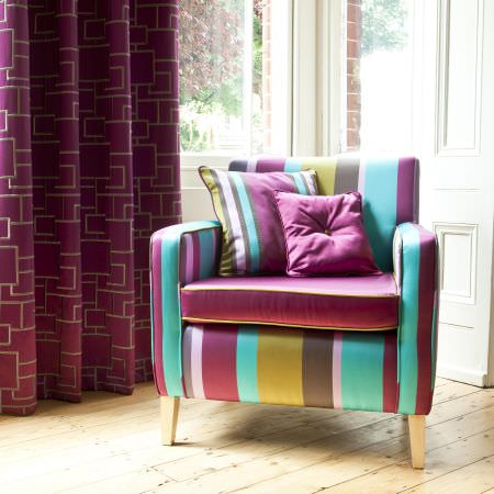 Prestigious Textiles -  Sophistication Fabric Collection - A dark purple curtain with random geometric designs, and a teal and purple upholstery with a striped and a plain cushion for a modern house