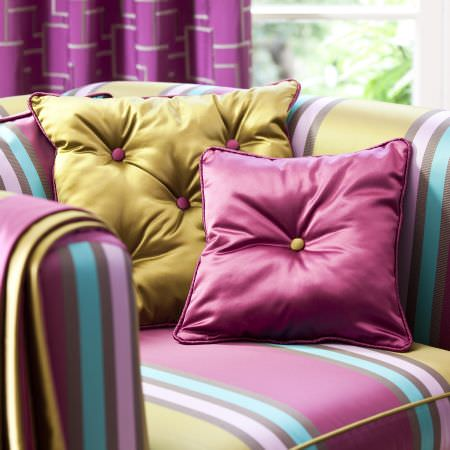 Prestigious Textiles -  Sophistication Fabric Collection - Close-up shot of a plain pink and a plain green cushion made of reflective fabrics on a striped upholstered armchair in a modern setting